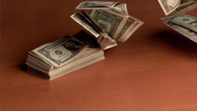 MS SLO MO Stack of dollar notes blowing away / San Francisco, California, USA