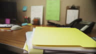 Stack of paperwork is dropped on an office desk, bounces and slides off.