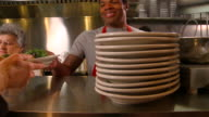 CU Stacked plates on restaurant counter/ PAN MS Cook placing money on counter, owner taking money/ MS PORTRAIT Man putting food on counter and smiling at camera/ Richmond, Virginia