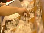Staff member sorts through cd racks in music shop