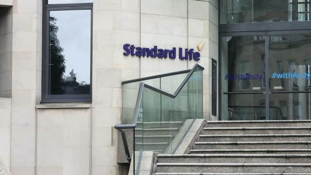 A Standard Life logo sits on a wall outside Standard Life House the headquarters of Standard Life Plc in Edinburgh UK on Saturday Aug 9 Pedestrians...