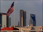 Stars and Stripes flag flying between modern buildings