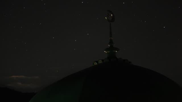 Stars wheel over mosque roof.