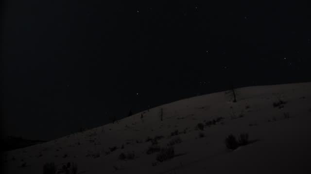 Stars wheel over snow covered hillside.