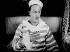 1925 B/W MS Startled man (Sidney Smith) waking up, fanning himself with his sailor hat, and gasping for air / Los Angeles County, California, USA