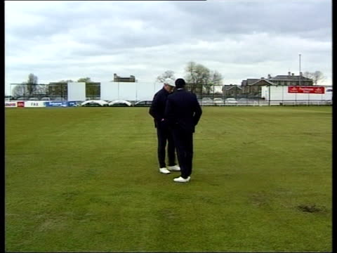 Bristol Gloomy Two men in suits and white shoes inspecting pitch ZOOM IN on man's shoes GV both along on pitch Seq players practising on pitch and in...