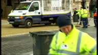 Queen arrival and departure Roadsweepers clearing up sand and horse manure from road outside Houses of Parliament