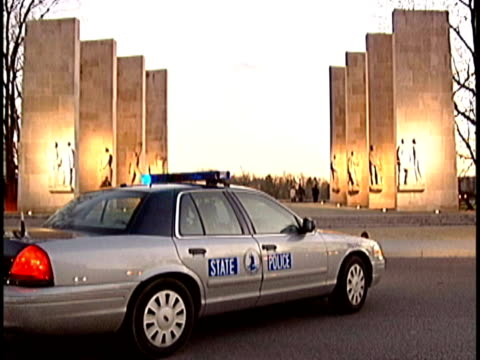 State police cars guarding the War Memorial at Virginia Tech / convoy of police cars driving along campus at dusk State police at Virginia Tech after...