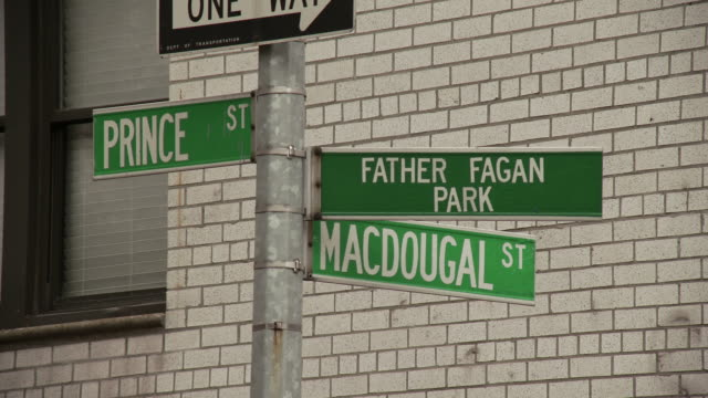Static close up shot of the street sign at the intersection between Prince and MacDougal street with a one way sign and a sign for Father Fagan Park