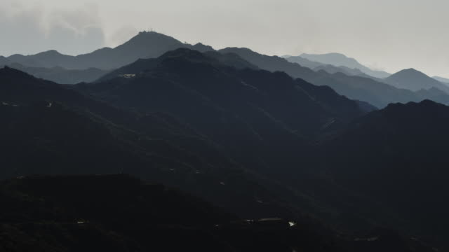Static frame, Malibu Mountains, smoke from distant brush fire billows up from behind far peak