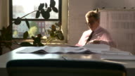 Static medium shot. Man works at a table late in the day by the window. He faces screen left.