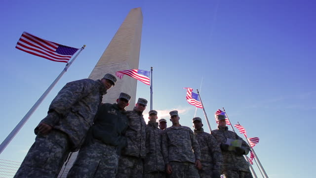 A static shot of a group of soldiers standing in front of the Washington Monument.