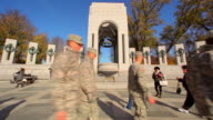 A static shot of a group of soldiers walking in front of the World War II Memorial.