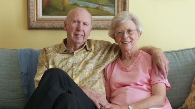 A static shot of a happy elderly couple sitting close to each other on a grey couch.