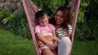 Static shot of a woman and child in a pink hammock.