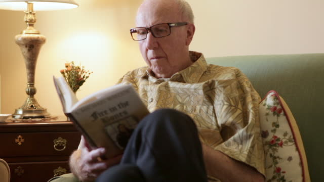 A static shot of an elderly man reading a book on a couch.