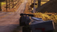 Static shot of country road, mailboxes and rail road crossing.