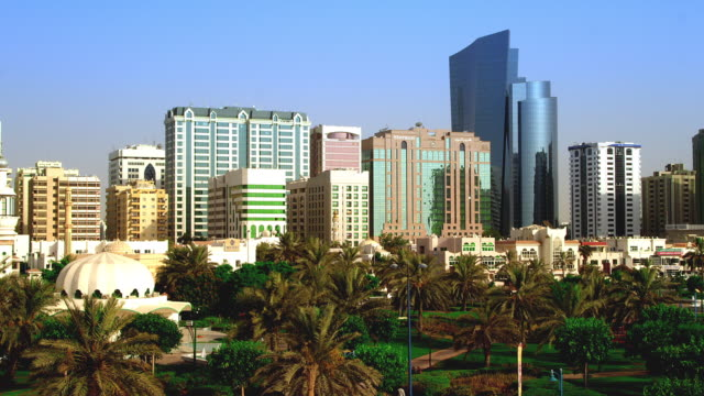 Static shot of part of Abu Dhabi skyline, with ADIA Tower background and gardens foreground.
