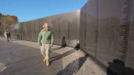 A static shot of soldiers walking past a wall of names of deceased soldiers in Wahington DC.
