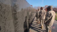 A static shot of the back of a group of soldiers walking by the Vietnam War Memorial.