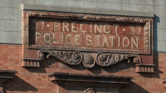 Static shot of the grungy, faded sign above the 37 precinct police station against the brick building the bronx during the day