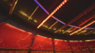 Static shot of the red bulbs of a fairground waltzer ride flashing on and off, creating abstract patterns on the plastic windows behind, UK.