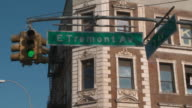 Static shot of the sign at the intersection of East Tremont Avenue and 3rd Avenue against a clear blue sky and an apartment building during the day in the bronx