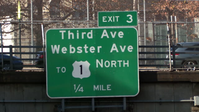 Static shot of the sign for exit 3 during the day on the cross bronx expressway for third ave and webster ave in the bronx while pedestrians walk by parked cars behind a fence in the background