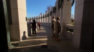 A static shot of two soldiers standing in the shadows of the World War II Memorial.