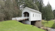 Static shot of white covered bridge with evergreens in background.