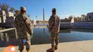 A static shot with a lens flare of the back of two soldiers at the WWII Memorial.