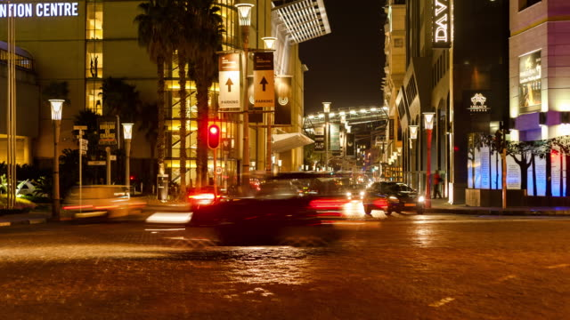 Static timelapse at night at a busy intersection of the nightlife and people buzzing in Johannesburg, South Africa at the Sandton Convention Centre