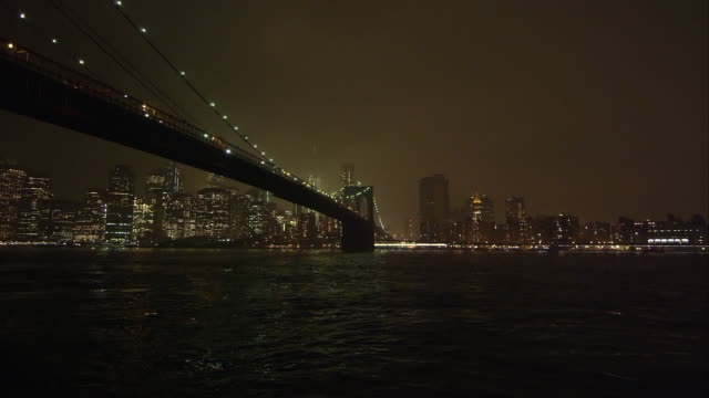 Static view at night overlooking the East River and the Brooklyn Bridge.
