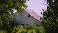 Static view of old white barn through the trees.