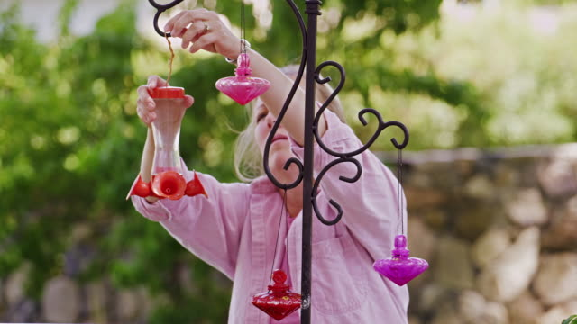 Static view of woman hanging up hummingbird feeders.