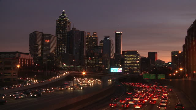 Static, wide shot of the Atlanta Skyline at night with traffic flowing below.