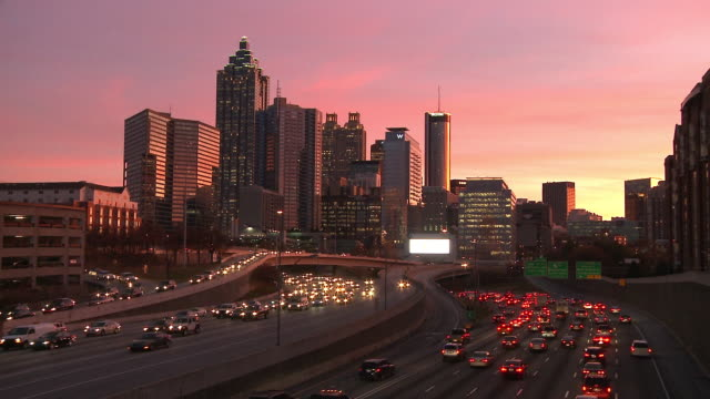 Static, wide, timelapse shot of the Atlanta Skyline with traffic below as the sun goes down.