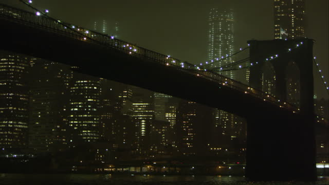 Static zoomed view at night overlooking the East River and the Brooklyn Bridge.