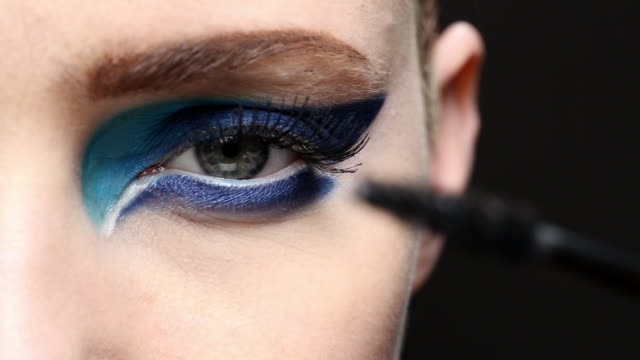 Statiionary shot of the models eye applying mascara.