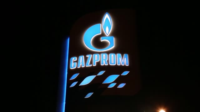 A station attendant refuels a customers vehicle on the forecourt of an OAO Gazprom Neft gas station in Belgrade Serbia on Thursday Jan 15 illuminated...
