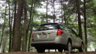 Station wagon backing up and parking in forest / couple getting out of car and removing inner tubes from trunk / shutting trunk and walking off with inner tubes / Farmington River, Connecticut