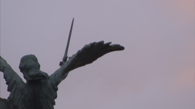 A statue in Rome depicts an angel wielding a sword.