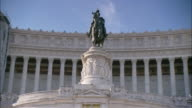 A statue of a rider on a horse stands on a pedestal near a columned building at the Vatican.