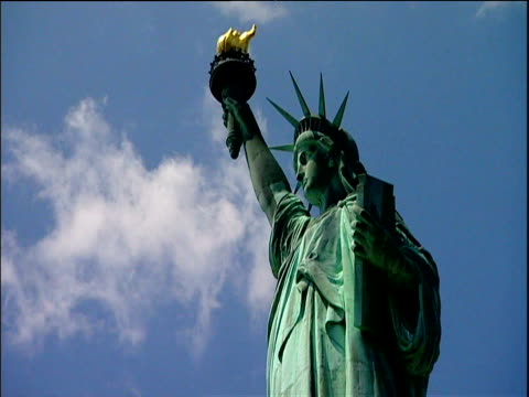 Statue of Liberty against blue sky holding Torch of Enlightenment and Tablet Ellis island New York