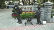 WS Statue of man with camcorder and woman with pram in park, Guangzhou, China
