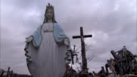 A statue of the Virgin Mary with outstretched hands at the Hill of Crosses. Available in HD.