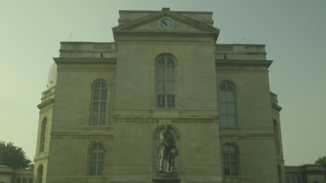 A statue of Urbain Le Verrier stands proudly in front of the Observatoire de Paris as the second hand on a clock above turns slowly round, fifth arrondissement, Paris, France.