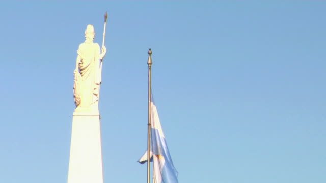 MS Statue on top of Pyramid de Mayo and Argentinean flag against clear sky, Plaza de Mayo, Buenos Aires, Argentina