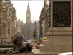 Statues of lions at base of Nelson's Column in Trafalgar Square with Whitehall stretching into distance and Big Ben in background