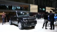 Steady shot of a Land Rover SUV on display at the 2014 Geneva Auto Show in Palexpo Geneva Switzerland as media members at visitors inspect the model...